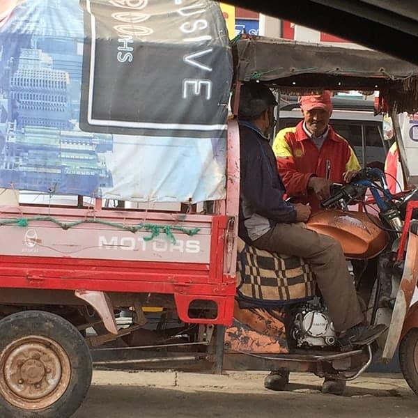 Deelnemer van het verkeer in Marokko, een brommer met een karretje erachter