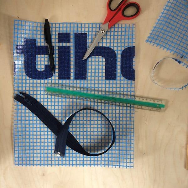 Stuk bouwplastic met schaar, pen, rits en lineaal om pennenetui van te maken