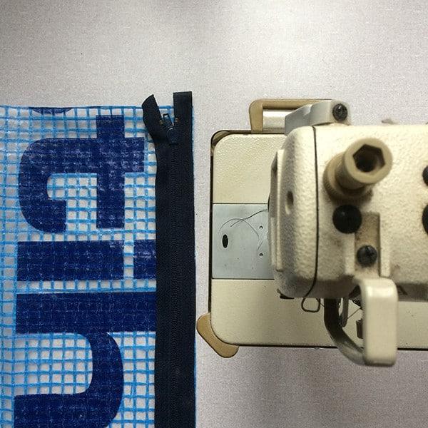 rits met stuk bouwplastic naast een naaimachine om een pennenetui van te maken