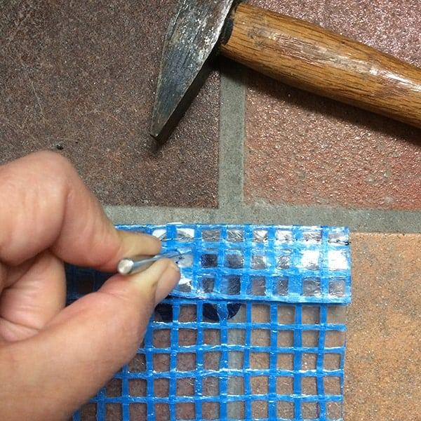 het inslaan van de drukknopen bij het zelf te maken portemonneetje