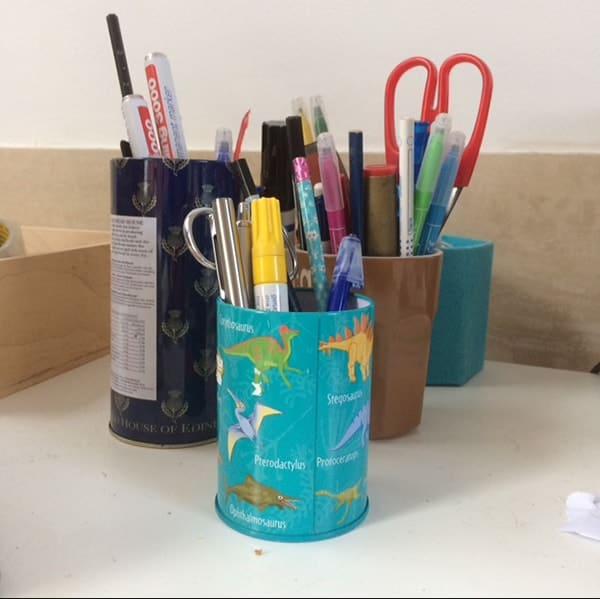 pennen, stiften en scharen in blikjes bijeen op een bureau