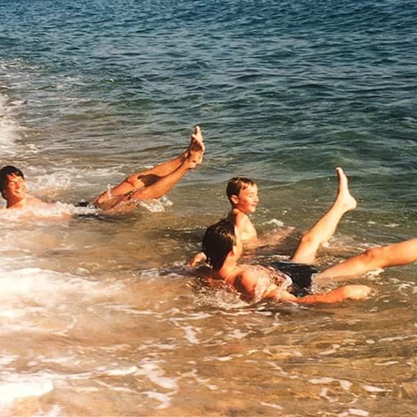 3 jongens hebben lol in de branding van de zee in Spanje