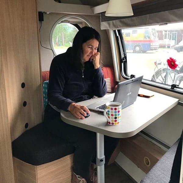 Jeannet zit hier aan haar laptopje te werken in de caravan