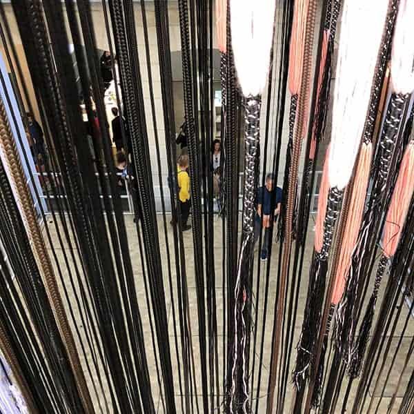 De textiele installatie van hangende repen stof van wel 16 meter van Hella Jongerius in het Lafayette Anticipations in Parijs