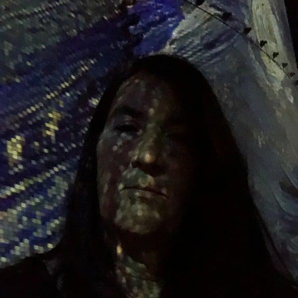 Mijn gezicht beschenen in het Atelier des Lumières door een Van Gogh schilderij