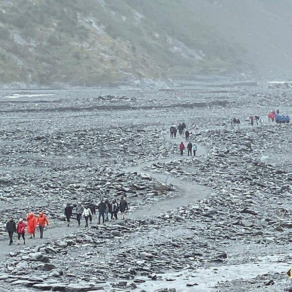 Wandelen door een opgedroogde rivierbedding naar de Frans Jozef Gletsjer