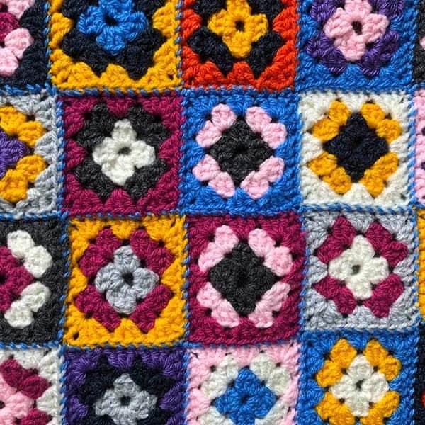 Een bonte mix van oma vierkantjes om een granny square kussen van te maken