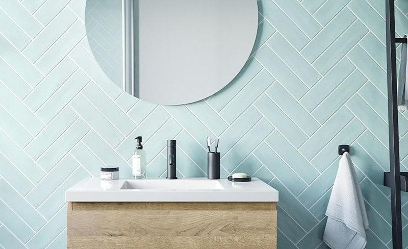 Een ronde badkamerspiegel in een Scandinavische badkamer